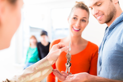 Accommodation broker giving home key to family